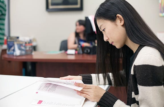 Alexander College Student Reading in Library
