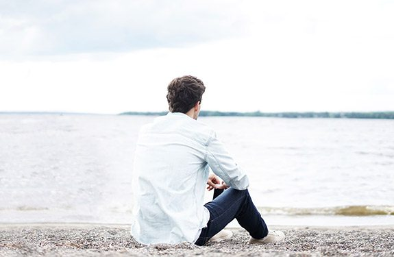 College student sitting at beach looking at ocean