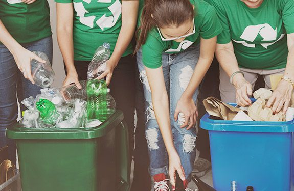 Students separating and recycling items into the correct bins