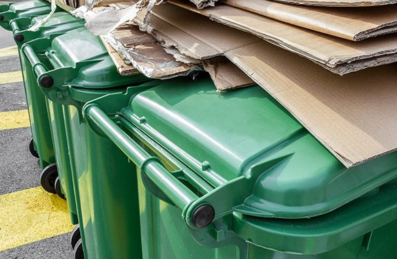 Green recycling bins with cardboard stacked on top