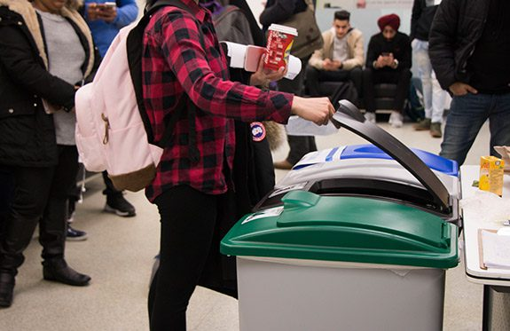 Alexander College student recycling coffee cup