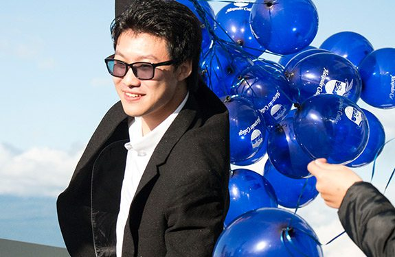 international student at Alexander College carrying balloons to graduation ceremony