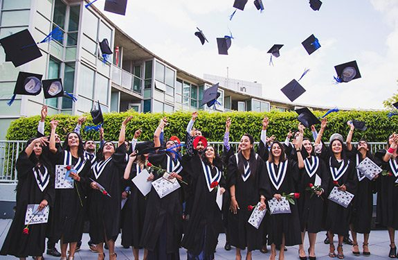 Students throwing their graduation caps at the Alexander College graduation ceremony after finishing their university transfer program