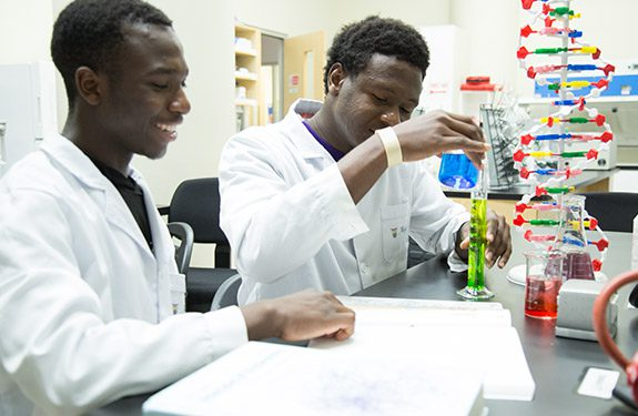 Two students studying chemistry while mixing solutions