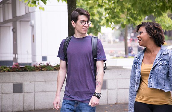 Two international students in Vancouver discussing English requirements at Alexander College while enjoying a walk