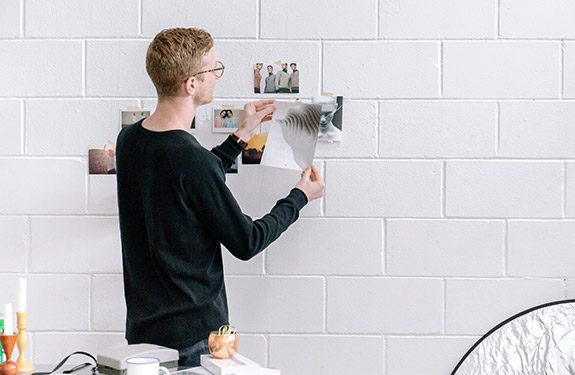 Man at work adding images on a brick wall