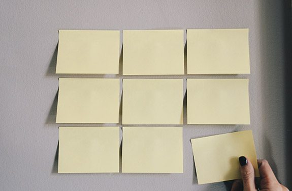 Student placing sticky notes on wall to help with job search