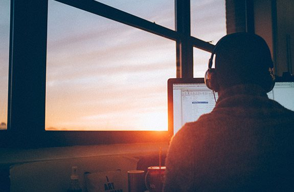 Man working on the computer while the sun is rising