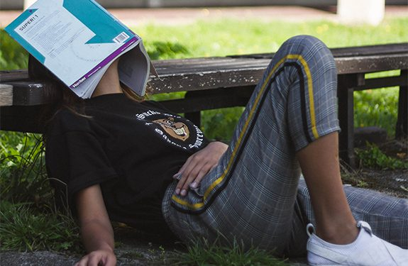 Student leaning against bench with book resting on face exhausted of studying