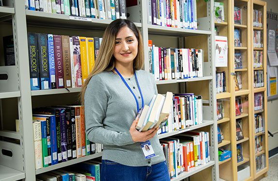 Alexander College student checking out books at campus bookstore